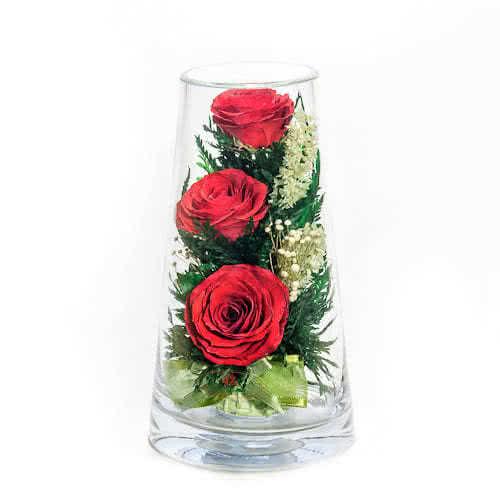 Красные розы в зеленой корзине в высоком конусообразном цилиндре