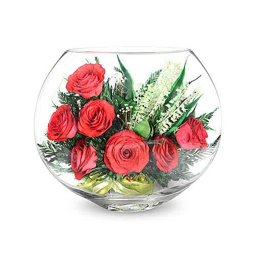 Красные розы в зеленой корзине в малой плоской круглой вазе