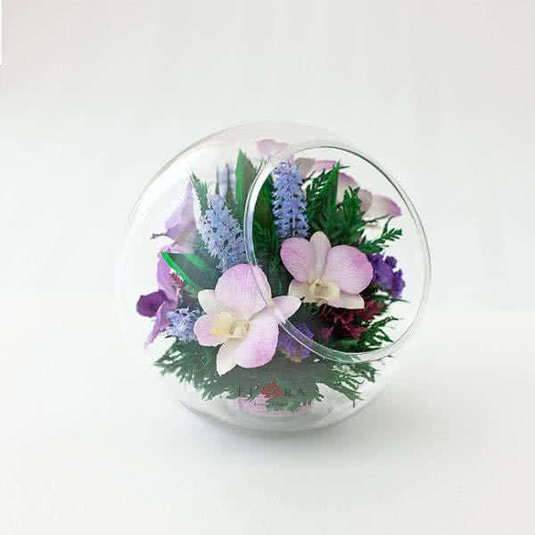 Сиреневые орхидеи в большой круглой вазе со скошенным верхом