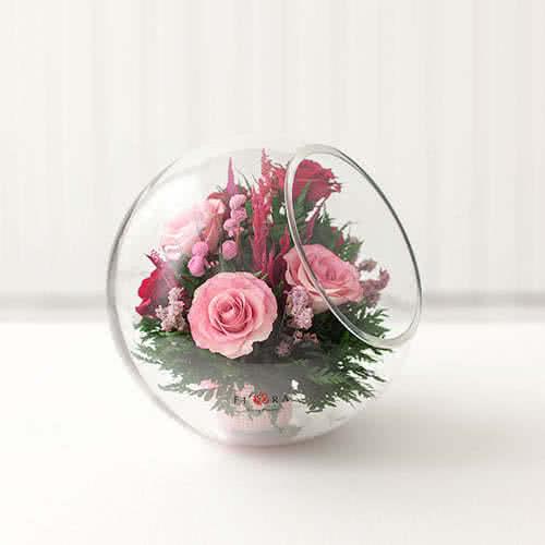 Лиловые и светло-розовые розы в большой круглой вазе со скошенным верхом