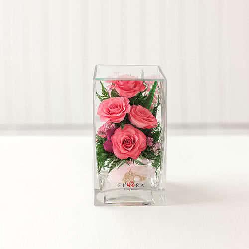 Ярко-розовые розы в средней кубической вазе