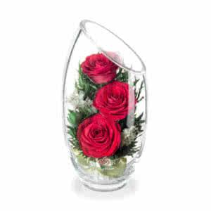 Красные розы в малой овальной вазе со скошенным верхом